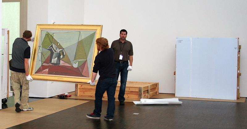 "In this March 17, 2009 photo, movers carry Pablo Picasso's ""Flower Vase on a Table,"" through the Figge galleries in Davenport, Iowa. Most of the works in the ""A Legacy for Iowa..."" exhibition were moved into the Figge that day. The University of Iowa received permission Wednesday, June 5, 2013, to develop plans for a new museum to store its premier collection of fine art, which has largely been stored off-campus since a 2008 flood. (AP Photo/Iowa City Press-Citizen) NO SALES"