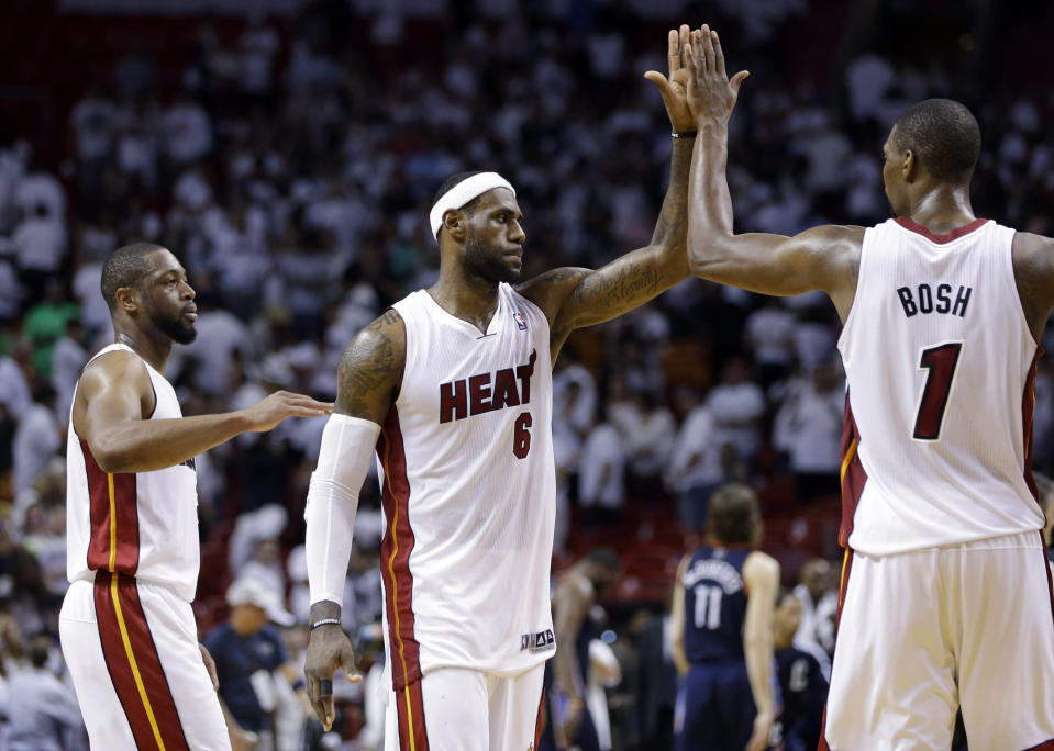 FILE - In this April 23, 2014 file photo, Miami Heat's LeBron James (6) high-fives Chris Bosh (1) after the Heat defeated the Charlotte Bobcats 101-97 in Game 2 of an opening-round NBA basketball playoff series in Miami. At left is Dwyane Wade. A person familiar with the situation tells The Associated Press that James has decided to opt out of the final two years of his contract with the Heat and become a free agent on July 1. Opting out does not mean James has decided to leave the Heat, said the person, who spoke on condition of anonymity because neither the four-time NBA MVP nor the team had made any public announcement. (AP Photo/Lynne Sladky, File)