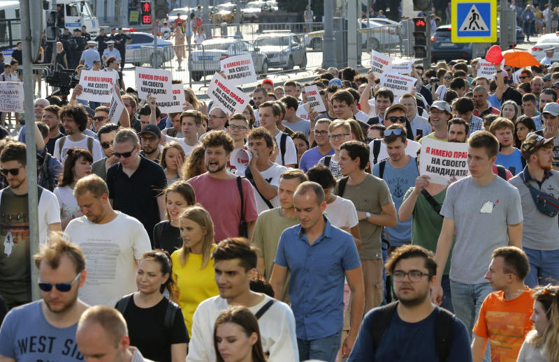 """FiLE - In this file photo dated Saturday, July 27, 2019, protesters hold posters that read: """"I have the right to my candidate"""" during an unsanctioned rally in the center of Moscow, Russia.  Moscow's children's rights ombudsman and other public figures Wednesday Aug. 7, 2019, have reacted with outrage to Russian prosecutors' moves to strip a couple of custody of their 1-year old son for allegedly taking him to this unauthorized protest on July 27. (AP Photo/Alexander Zemlianichenko, FILE)"""