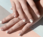 """At Seattle's <a href=""""https://www.instagram.com/p/Bz0vgF0JLmU/"""" rel=""""nofollow noopener"""" target=""""_blank"""" data-ylk=""""slk:Urban Nail Box"""" class=""""link rapid-noclick-resp"""">Urban Nail Box</a>, pared-back designs like this negative space nail art rule. """"When it comes to the most minimalist of mani lovers, we can never go wrong with the combination of black and white,"""" says founder Rachel Dang. """"Thin black stripes paired with a negative white base create this beautiful art piece."""" The trick is to leave some parts of the nail bare for an eye-catching effect."""