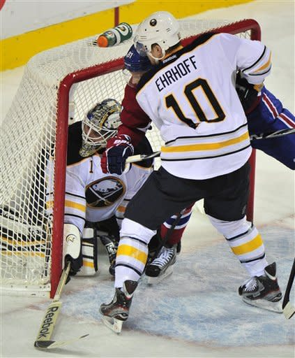 Buffalo Sabres goalie Jhonas Enroth kneels in the net as teammate defenseman Christian Ehrhoff takes out Montreal Canadiens' Lars Eller during the first period of an NHL hockey game, Monday, Nov. 14, 2011, in Montreal. (AP Photo/The Canadian Press, Paul Chiasson)