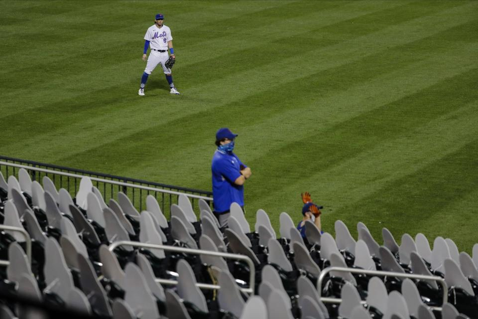 New York Mets left fielder Jeff McNeil looks at grounds crew members standing among cut-outs of fans during the second inning of a baseball game against the Miami Marlins Friday, Aug. 7, 2020, in New York. (AP Photo/Frank Franklin II)