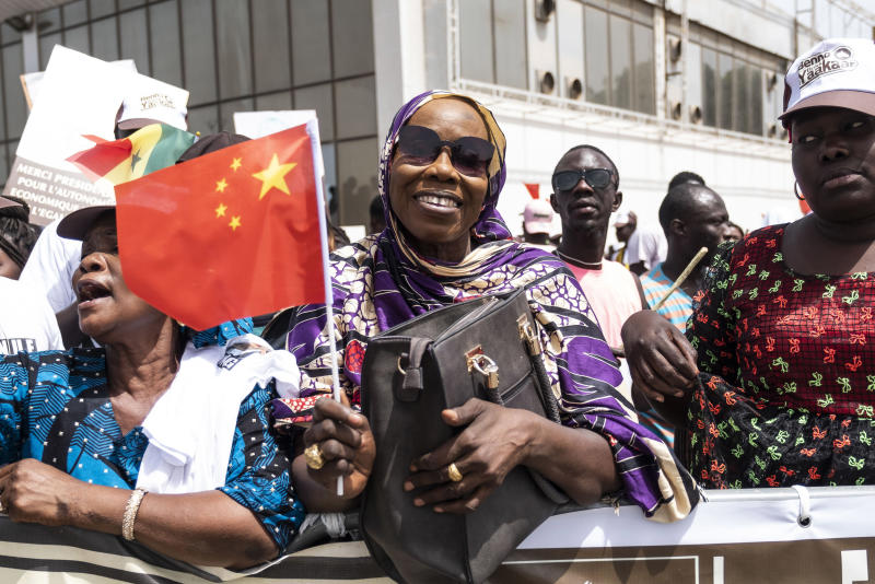 A Senegal resident welcomes Chinese President Xi Jinping in Dakar, Senegal, Saturday, July. 21, 2018. Chinese President Xi Jinping arrives in Africa on Saturday on a four-nation visit seeking deeper military and economic ties. (AP Photo/Xaume Olleros)