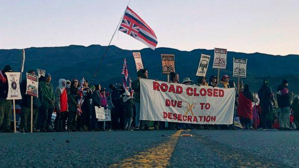 PHOTO: Demonstrators block a road at the base of Hawaii's tallest mountain, July 15, 2019, in Mauna Kea, Hawaii, to protest the construction of a giant telescope on land that some Native Hawaiians consider sacred. (Caleb Jones/AP)