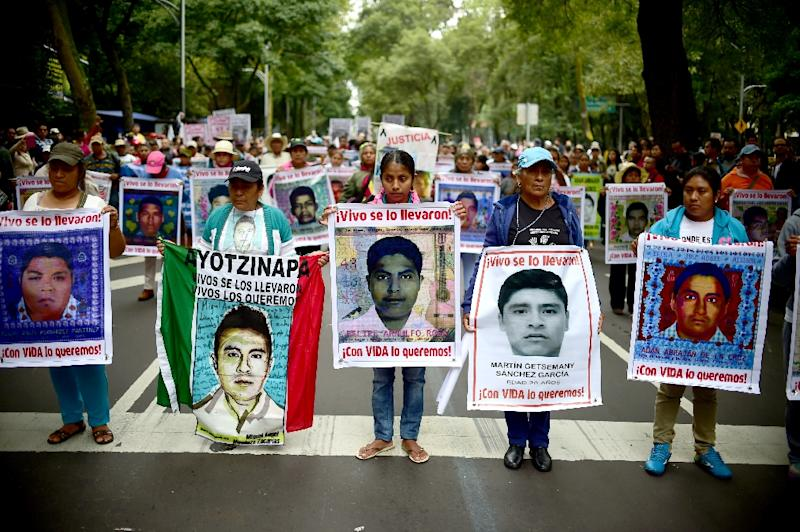 People hold posters of disappeared students during a protest in Mexico city, on September 26, 2015, to commemorate the first anniversary of Ayotzinapa school students disappearance