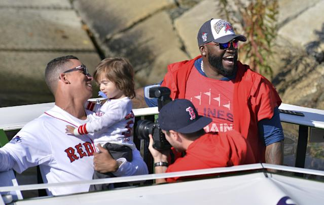 Boston Red Sox's Quintin Berry, left, and David Ortiz ride on an amphibious duck boat on the Charles River Saturday, Nov. 2, 2013, in Cambridge, Mass., during a rolling victory parade celebrating the team's World Series title. (AP Photo/Josh Reynolds)