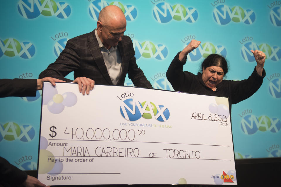 TORONTO, ON - APRIL 8: Senior VP Lottery Ken McKenzie presents Maria Carreiro with the $40 million cheque. Maria Carreiro won the $40 million LOTTO MAX jackpot on the Friday April 5 draw. She says that after thirty ears of marriage she is finally going on her dream Hawaiian honeymoon. Carlos Osorio/Toronto Star via Getty Images)