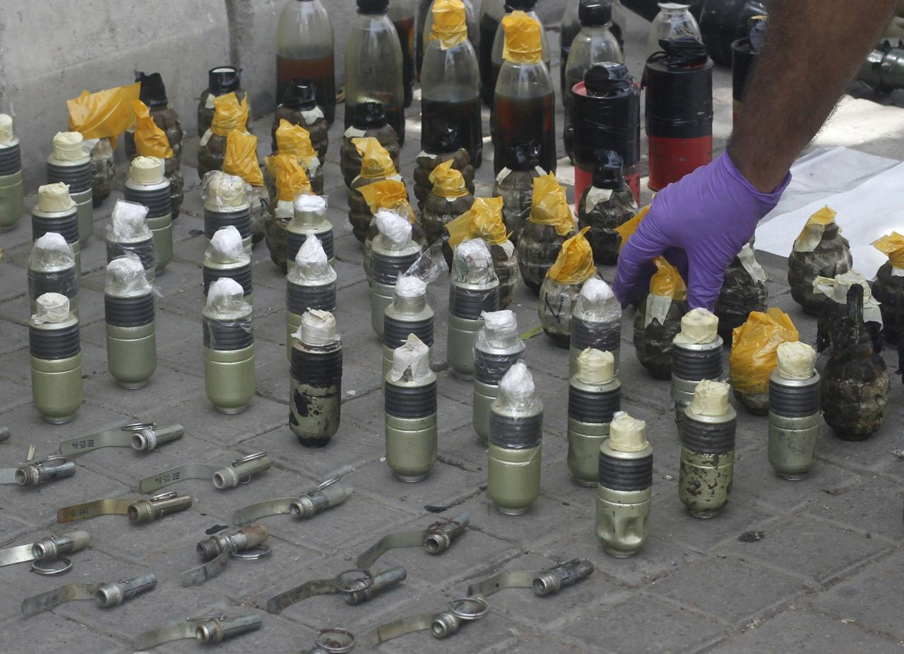 A member of the Bomb Disposal Squad (BDS) places hand grenades in a line after defusing them along a sidewalk outside Jinnah International Airport in Karachi June 9, 2014. Taliban militants disguised as security forces stormed Pakistan's busiest airport on Sunday and at least 27 people were killed in a night-long battle at one of the country's most high-profile targets. REUTERS/Athar Hussain (PAKISTAN - Tags: TRANSPORT CIVIL UNREST)