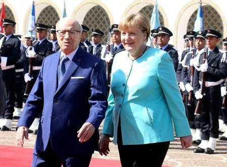 Tunisia's President Beji Caid Essebsi and German Chancellor Angela Merkel walk past a guard of honour at Carthage Palace in Tunis