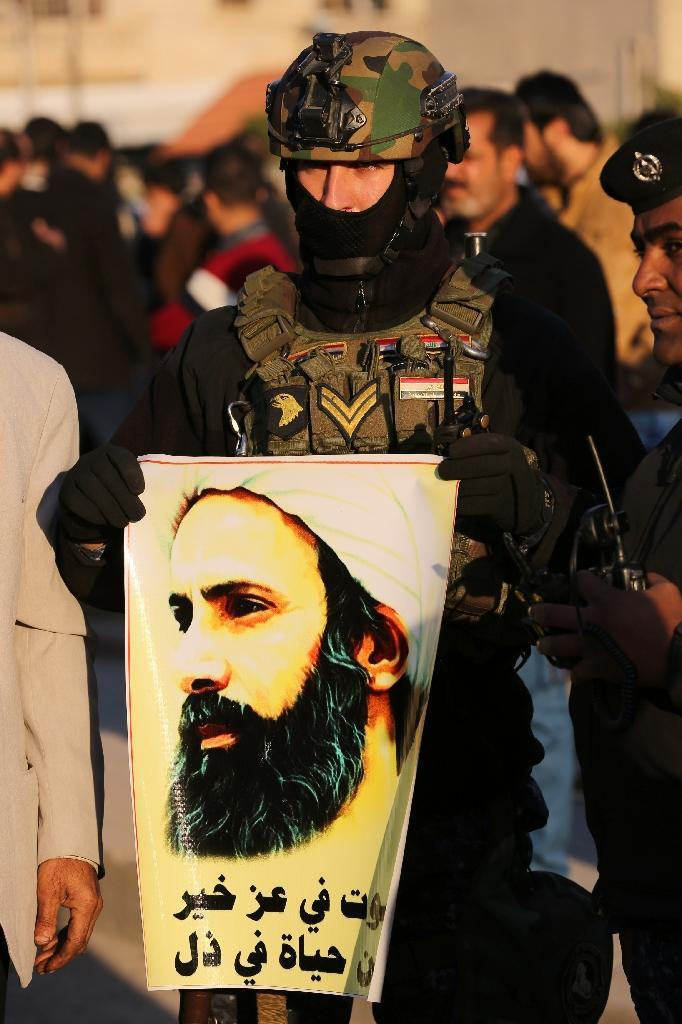 An Iraqi policeman holds a portrait of prominent Shiite Muslim cleric Nimr al-Nimr during a demonstration against his execution by Saudi authorities, on January 3, 2016, in the capital Baghdad (AFP Photo/Ahmad Al-Rubaye)