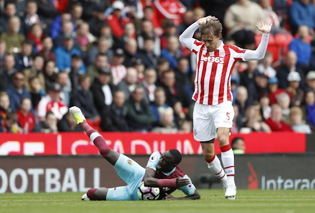 <p>Stoke City's Marc Muniesa in action with West Ham United's Cheikhou Kouyate </p>