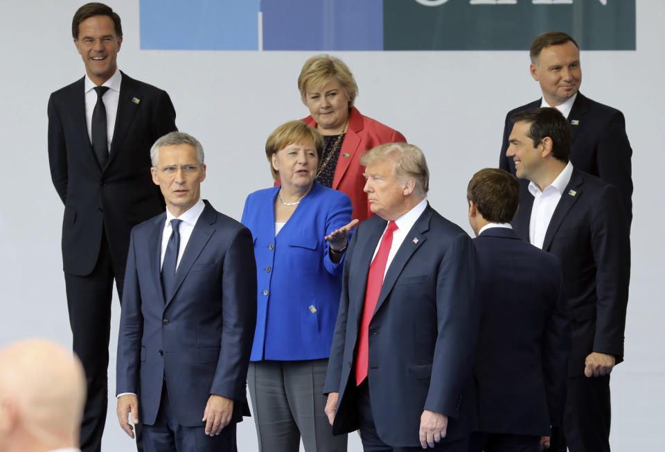 FILE - In this July 11, 2018 file photo, German Chancellor Angela Merkel, centre left, NATO Secretary General Jens Stoltenberg, 2nd left, US President Donald Trump , center right, French President Emmanuel Macron, right back to camera, , and Greek Prime Minister Alexis Tsipras, right, stand prior to a group photo ahead of the opening ceremony of the NATO summit, in Brussels. Now that Britain has left the bloc, the EU is looking to clarify how it carries out a joint foreign policy for the remaining 27 nations. (Ludovic Marin, Pool via AP, File)
