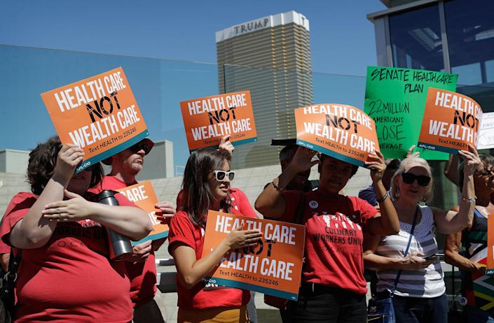 <p>People protest with the Trump International hotel in the background, Tuesday, June 27, 2017, in Las Vegas. Union officials in Nevada, community members and others gathered Tuesday at a pedestrian bridge over the Las Vegas Strip to urge Republican U.S. Sen. Dean Heller to continue to oppose the current GOP health care bill. (Photo: John Locher/AP) </p>
