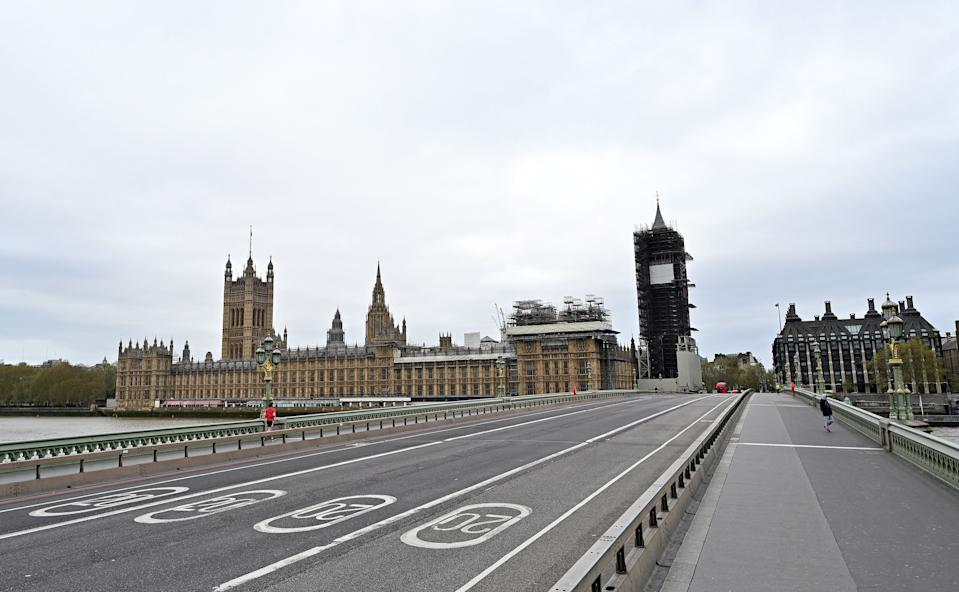 An empty Westminster Bridge is pictured in front of Britain's Houses of Parliament in central London on April 13, 2020, as life in Britain continues over the Easter weekend, during the nationwide lockdown to combat the novel coronavirus pandemic. - Virus-stricken British Prime Minister Boris Johnson thanked medics for saving his life after leaving hospital on Easter Sunday, as hundreds of millions of Christians observed the holiday under lockdown due to the coronavirus pandemic. More than half of humanity is confined at home as governments scramble to stop the COVID-19 pandemic, which has claimed more than 112,500 lives around the world. (Photo by Glyn KIRK / AFP) (Photo by GLYN KIRK/AFP via Getty Images)