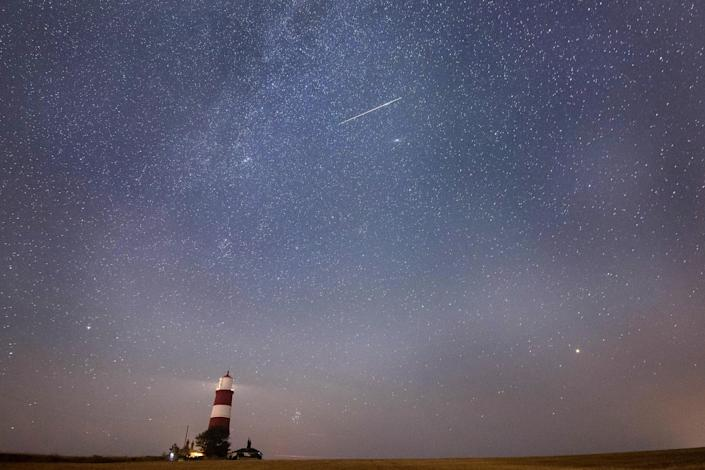 A meteor during the Perseid meteor shower seen over Happisburgh lighthouse in Norfolk, England. / Credit: Joe Giddens/PA Images via Getty Images