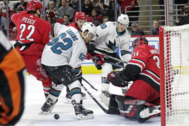 Carolina Hurricanes' Brett Pesce (22) and Petr Mrazek (34) of the Czech Republic defend the goal against San Jose Sharks' Kevin Labanc (62) and Marcus Sorensen (20) of Sweden during the first period of an NHL hockey game in Raleigh, N.C., Thursday, Dec. 5, 2019. (AP Photo/Chris Seward)