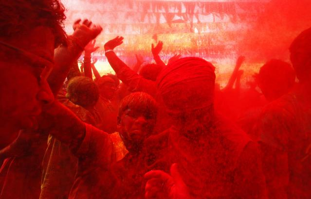 People daubed in colours dance as they celebrate Holi in the northeastern Indian city of Guwahati March 17, 2014. Holi, also known as the Festival of Colours, heralds the beginning of spring and is celebrated all over India. REUTERS/Utpal Baruah (INDIA - Tags: SOCIETY RELIGION)