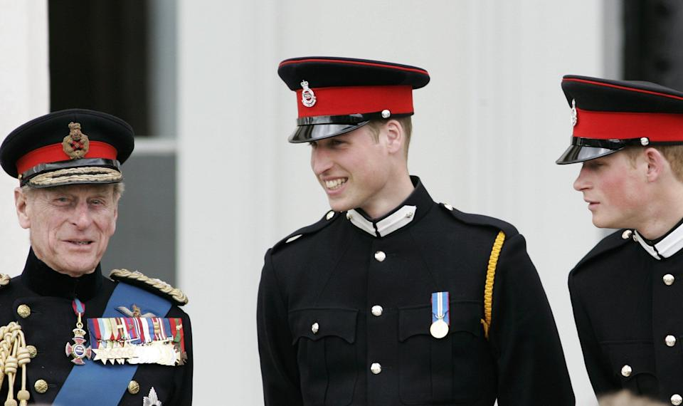 Prince Philip talks with his grandsons Prince William and Prince Harry at the Sovereign's Parade at Sandhurst Military Academy on April 12, 2006, in Surrey, England. (Photo: Tim Graham via Getty Images)