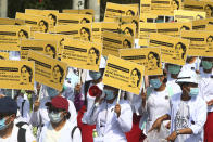Medicals students display images of deposed Myanmar leader Aung San Suu Kyi during a street march in Mandalay, Myanmar, Friday, Feb. 26, 2021. In the country's second-largest city, anti-coup protesters took to the streets Friday. By midday, security forces had blocked the main road in downtown Mandalay to prevent the protesters from gathering. (AP Photo)