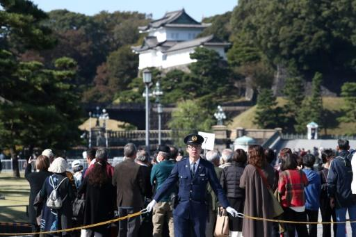 Police officers stand guard around Japan's Imperial Palace ahead of Sunday's parade