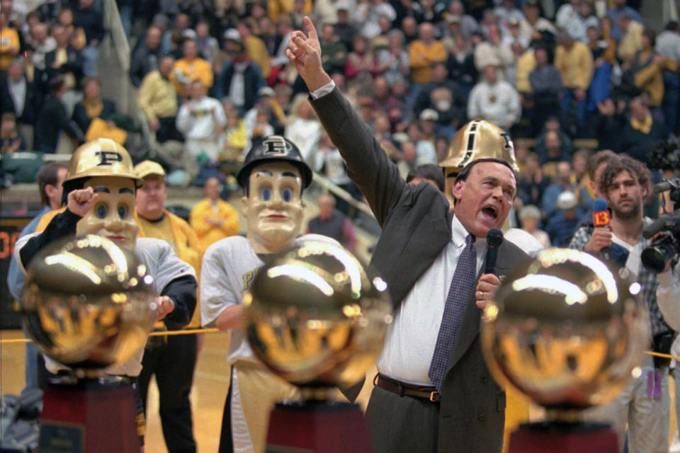 FILE - Purdue coach Gene Keady, framed by the three Big Ten Championship trophies, reacts to the crowd after capturing his third-straight Big Ten Championship by defeating Northwestern 79-56 in West Lafayette, Ind., in this Saturday, March 2, 1996, file photo. Tony Hinkle turned Butlers pass-and-cut offense of the 1920s into a coaching textbook for generations. Bob Knight and Gene Keady added their own revisions following Hinkle's forced retirement in 1970. Today, those three remain the gold standard of basketball innovation in Indiana, a state where successful coaches have spent more than a century testing novel concepts, breaking barriers and polishing philosophies before introducing them America. (AP Photo/Michael Conroy, File)