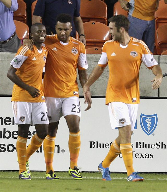Houston Dynamo midfielder Boniek Garcia (27) is congratulated by midfielder Giles Barnes (23) and forward Will Bruin (12) after scoring on a penalty kick in the first half against the Montreal Impact during a knockout-round match in the MLS Cup soccer playoffs, Thursday, Oct. 31, 2013, in Houston. (AP Photo/Bob Levey)
