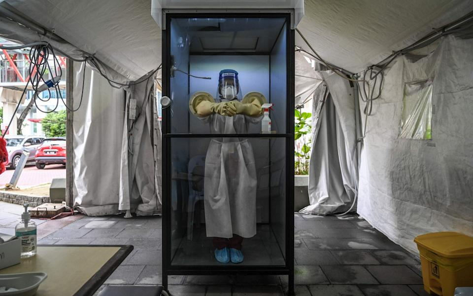 """A health worker stands inside a non-contact chamber called the """"CoV SHIELD"""" before taking swab samples to test for COVID-19"""