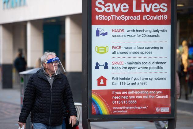 A man wearing a face shield walks past a coronavirus advice sign in Nottingham city centre. Nottinghamshire has been placed into Tier 2 of the new coronavrius restrictions with meeting socially banned indoors and the rule of six applying outdoors.