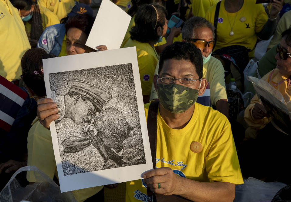 A supporter of Thai monarch displays an image of late King Bhumibol Adulyadej ahead of the arrival of King Maha Vajiralongkorn and Queen Suthida to participate in a candle lighting ceremony to mark birth anniversary of the late king at Sanam Luang ceremonial ground in Bangkok, Thailand, Saturday, Dec. 5, 2020. (AP Photo/Gemunu Amarasinghe)