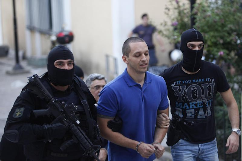 Lawmaker of the extreme far-right Golden Dawn party, Ilias Kasidiaris, is escorted by anti-terror police at the court, in Athens, Saturday, Sept. 28, 2013. Police arrested the leader of Greece's extreme-right Golden Dawn party and other top members on Saturday, in an escalation of a government crackdown after a fatal stabbing allegedly committed by a supporter. It is the first time since 1974 that sitting members of Parliament have been arrested. (AP Photo/Kostas Tsironis)