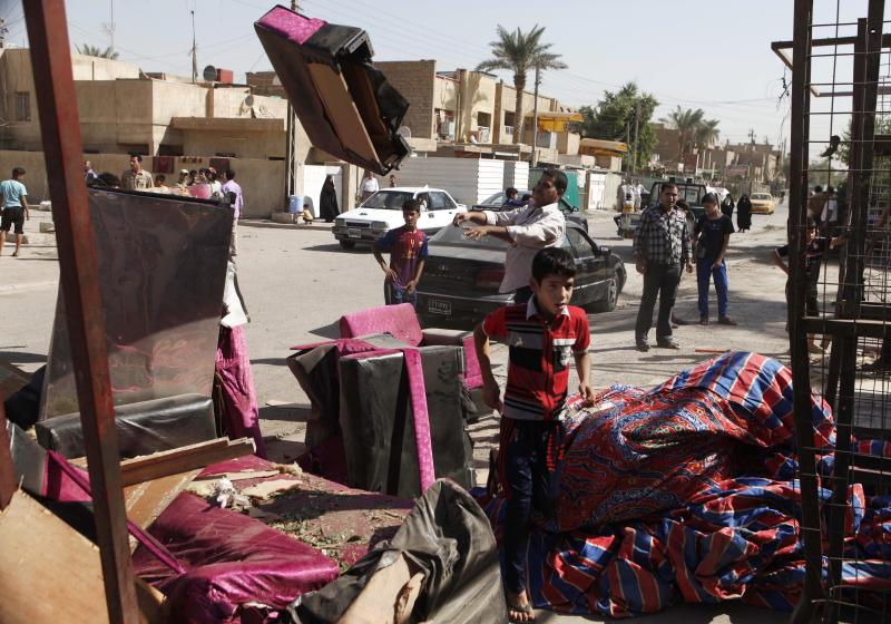 Iraqis inspect the scene of a car bomb attack in Baghdad, Iraq, Sunday, Sept. 30, 2012. A rapid-fire series of explosions in Baghdad while Iraqis were going to work on Sunday morning, killed and wounded scores of people, police said. (AP Photo/Karim Kadim)