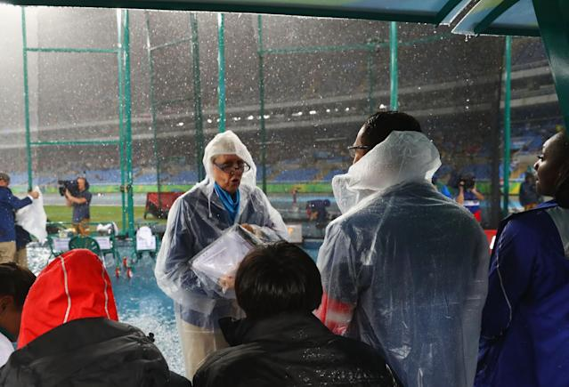 <p>Competitors wait under an awning as rain falls at the Olympic Stadium. (Getty) </p>