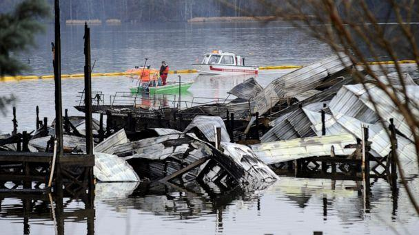 PHOTO: People on boats patrol near the charred remains of a dock following a fatal fire at a Tennessee River marina in Scottsboro, Ala., Jan. 27, 2020. (Jay Reeves/AP)