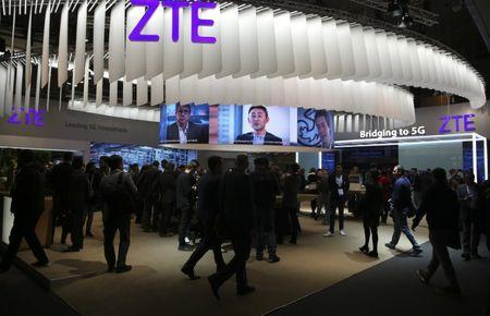 People stand at ZTE's booth during Mobile World Congress in Barcelona, Spain, February 27, 2017. REUTERS/Paul Hanna