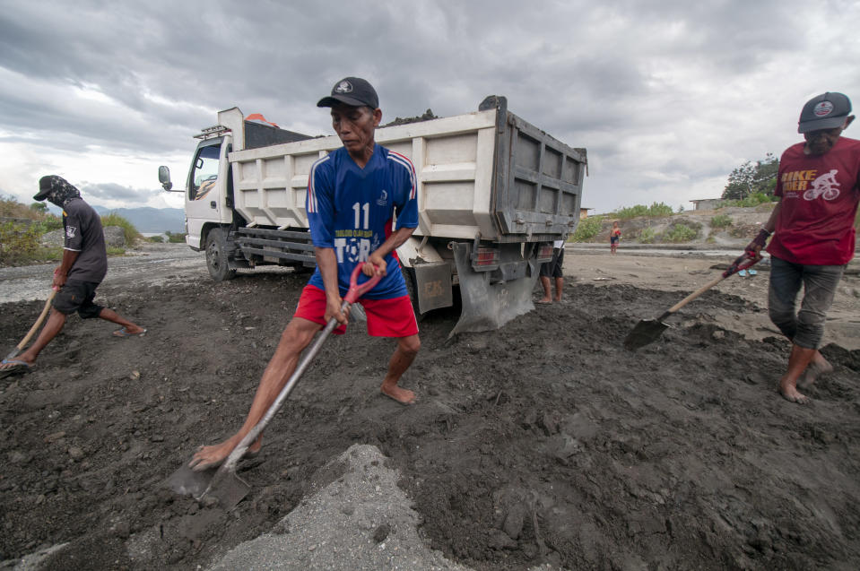 Workers shovel a mixture of sand and gravel onto trucks in the people's sand mining Palupi village, Palu, Central Sulawesi, Indonesia, February 24, 2019. Hundreds of people around the watershed depend on mining. Source: Basri Marzuki/NurPhoto via Getty Images.