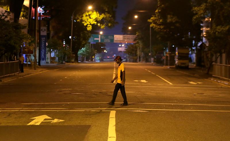 A Sri Lankan man walks across a deserted street during a curfew in Colombo, Sri Lanka, Sunday, April 21, 2019. More than two hundred people were killed and hundreds more injured in eight blasts that rocked churches and hotels in and just outside Sri Lanka's capital on Easter Sunday. (Photo: Eranga Jayawardena/AP)