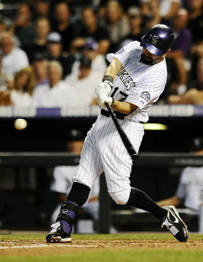 Colorado Rockies' Todd Helton hits a home run in the second inning of a baseball game against the Los Angeles Dodgers, Wednesday, Sept. 4, 2013, in Denver. (AP Photo/Chris Schneider)