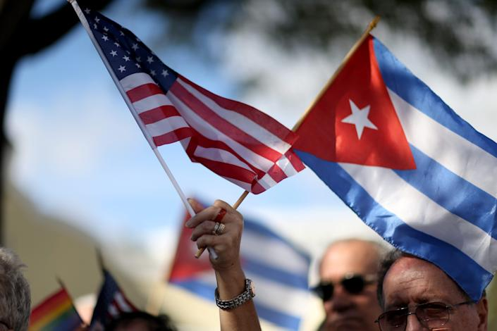 A protester holds American and Cuban flags during a demonstration at Jose Marti park on December 20, 2014, in Miami after President Obama announced his decision to normalize relations with Cuba.