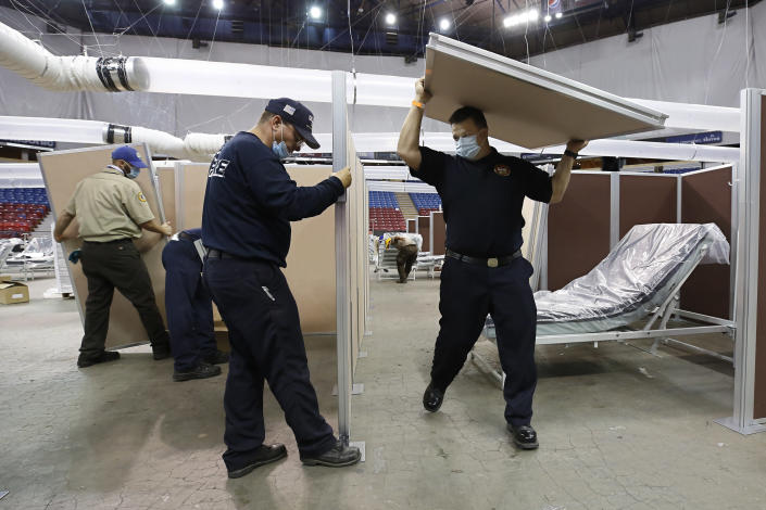 FILE — In this April 18, 2020, file photo, partitions are installed between beds as Sleep Train Arena is turned into a 400-bed emergency field hospital to help deal with the coronavirus, in Sacramento, Calif. California spent nearly $200 million to set up, operate and staff alternate care sites that ultimately provided little help when the state's worst coronavirus surge spiraled out of control last winter, forcing exhausted hospital workers to treat patients in tents and cafeterias. (AP Photo/Rich Pedroncelli, File)