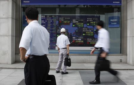 Pedestrians look at an electronic board showing the stock market indices of various countries outside a brokerage in Tokyo June 25, 2014. REUTERS/Yuya Shino
