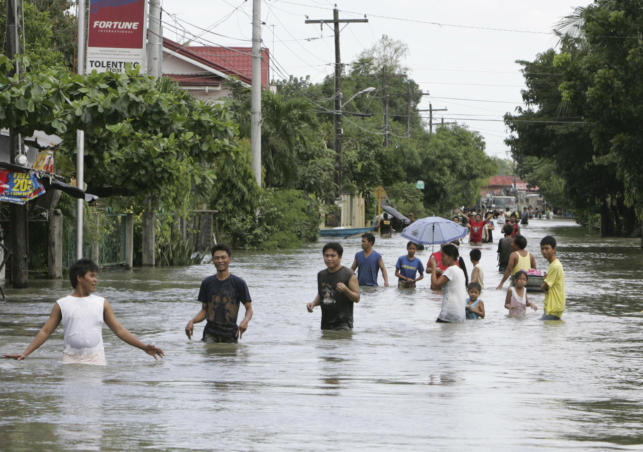 Residents wade through floodwaters at La Paz township, Tarlac province in northern Philippines, Thursday, Sept. 29, 2011, three days after typhoon Nesat lashed northeastern provinces and the Philippine capital Manila. The powerful typhoon, which is forecast to hit Hainan in China, caused extensive damage to agriculture and left at least 35 people dead. (AP Photo/Bullit Marquez)