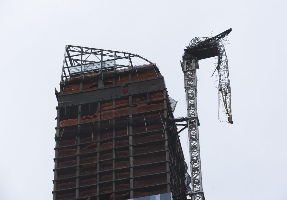 A construction crane atop a luxury high-rise dangles precariously over the streets after collapsing in high winds from Hurricane Sandy, Monday, Oct. 29, 2012, in New York. Hurricane Sandy bore down on the Eastern Seaboard's largest cities Monday, forcing the shutdown of mass transit, schools and financial markets, sending coastal residents fleeing, and threatening a dangerous mix of high winds, soaking rain and a surging wall of water up to 11 feet tall. (AP Photo/John Minchillo)