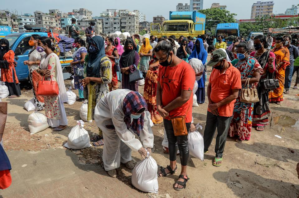 Transgender people wait standing to collect relief material during a government-imposed lockdown as a preventive measure against the COVID-19 coronavirus, in Dhaka on May 6, 2020. (Photo by MUNIR UZ ZAMAN / AFP) (Photo by MUNIR UZ ZAMAN/AFP via Getty Images)