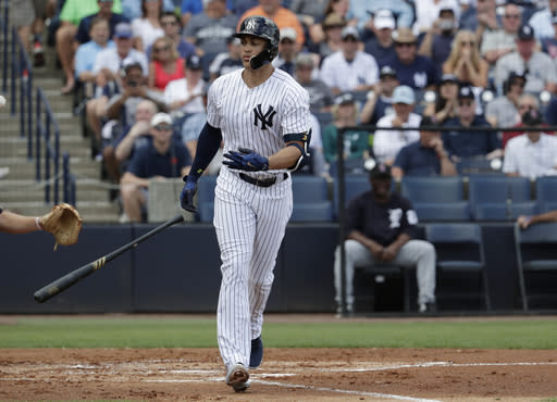 New York Yankees' Giancarlo Stanton tosses his bat after drawing a walk during the first inning of a baseball spring exhibition game against the Detroit Tigers, Friday, Feb. 23, 2018, in Tampa, Fla. (AP Photo/Lynne Sladky)