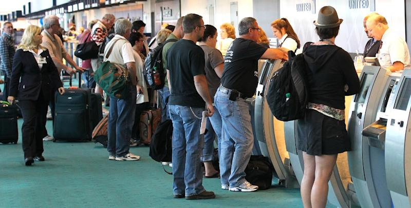 FILE - In a Friday, May 25, 2012 file photo, holiday travelers gather at the ticket counter at Portland International Airport, in Portland, Ore. AAA estimates that another 2.3 million travelers will fly for the 2013 Memorial Day holiday, down 8 percent from last year. (AP Photo/Rick Bowmer, File)