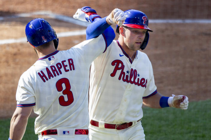 Philadelphia Phillies Rhys Hoskins, right, is congratulated by Bryce Harper (3) after he hit a home run during the first inning of a baseball game, Wednesday, April 7, 2021, in Philadelphia. (AP Photo/Laurence Kesterson)