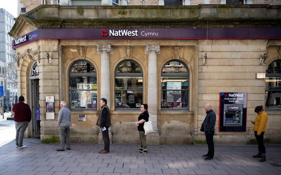 Customers queue outside Natwest bank, practising social distancing, on March 24, 2020 in Cardiff - Matthew Horwood/Getty Images Contributor