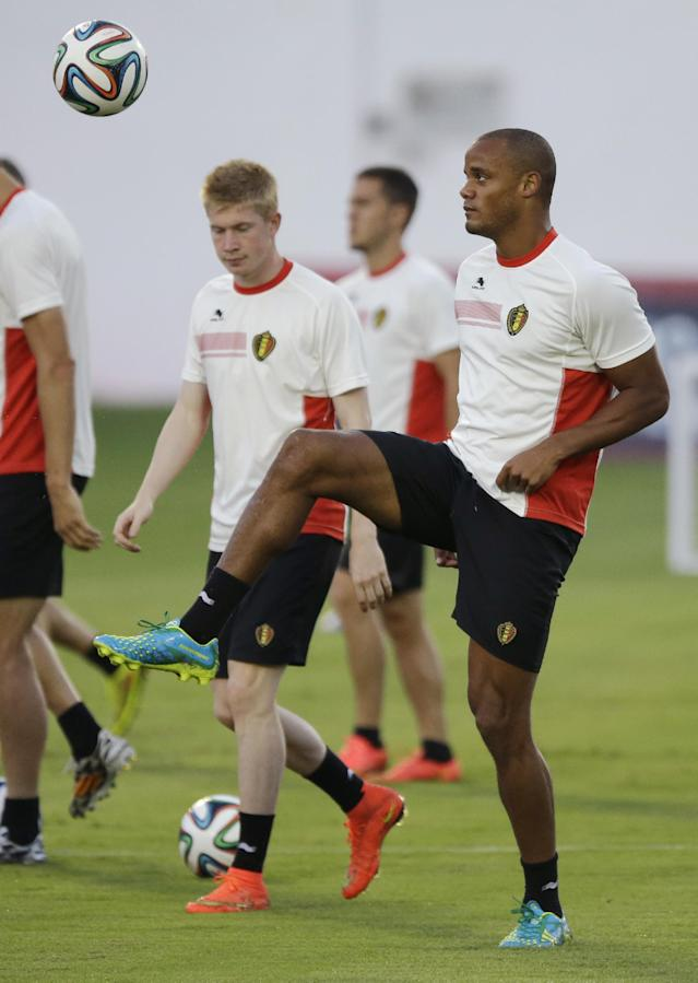 Belgium's captain Vincent Kompany, right, who is recovering from an injury, keeps a ball up as he takes part in a training session at Estadio Manoel Barradas the day before the World Cup round of 16 soccer match between Belgium and USA at Arena Fonte Nova in Salvador, Brazil, Monday, June 30, 2014. (AP Photo/Matt Dunham)