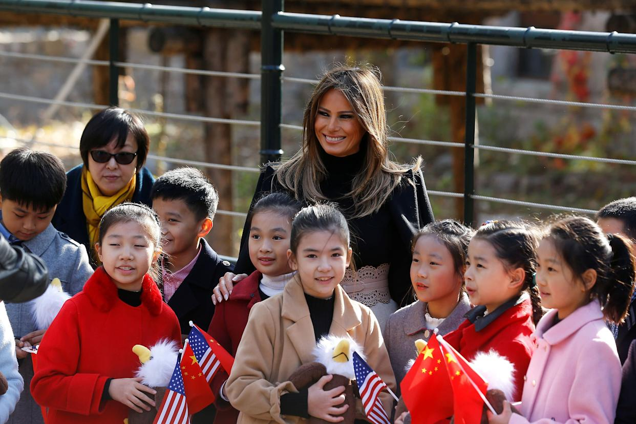 Melania Trump smiles with children holding U.S. and China flags as she visits Beijing Zoo.