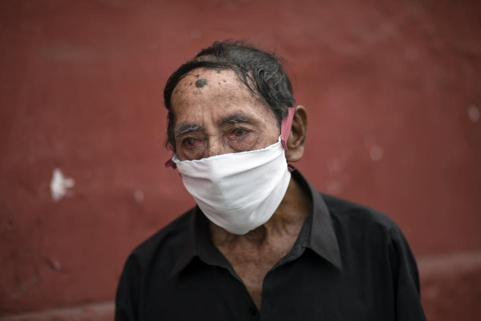 Ciro Orlando Gijon, 78, wearing a protective face mask as a precaution against the spread the new coronavirus, waits to apply for shelter at the Plaza de Toros de Acho bullring, in Lima, Peru, Tuesday, March 31, 2020. The mayor of Lima reported that the plaza will provide shelter and balanced meals for some of the city's homeless amid the new coronavirus pandemic. (AP Photo/Rodrigo Abd)
